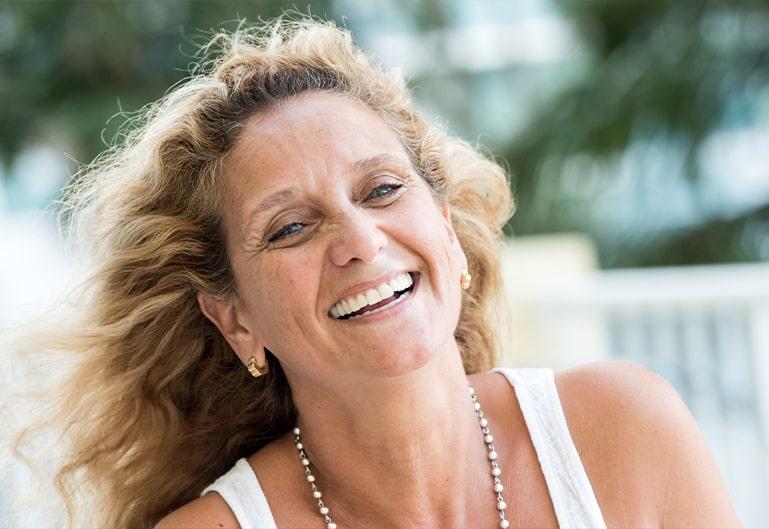 Glücklich lachende Frau mit Perlenkette